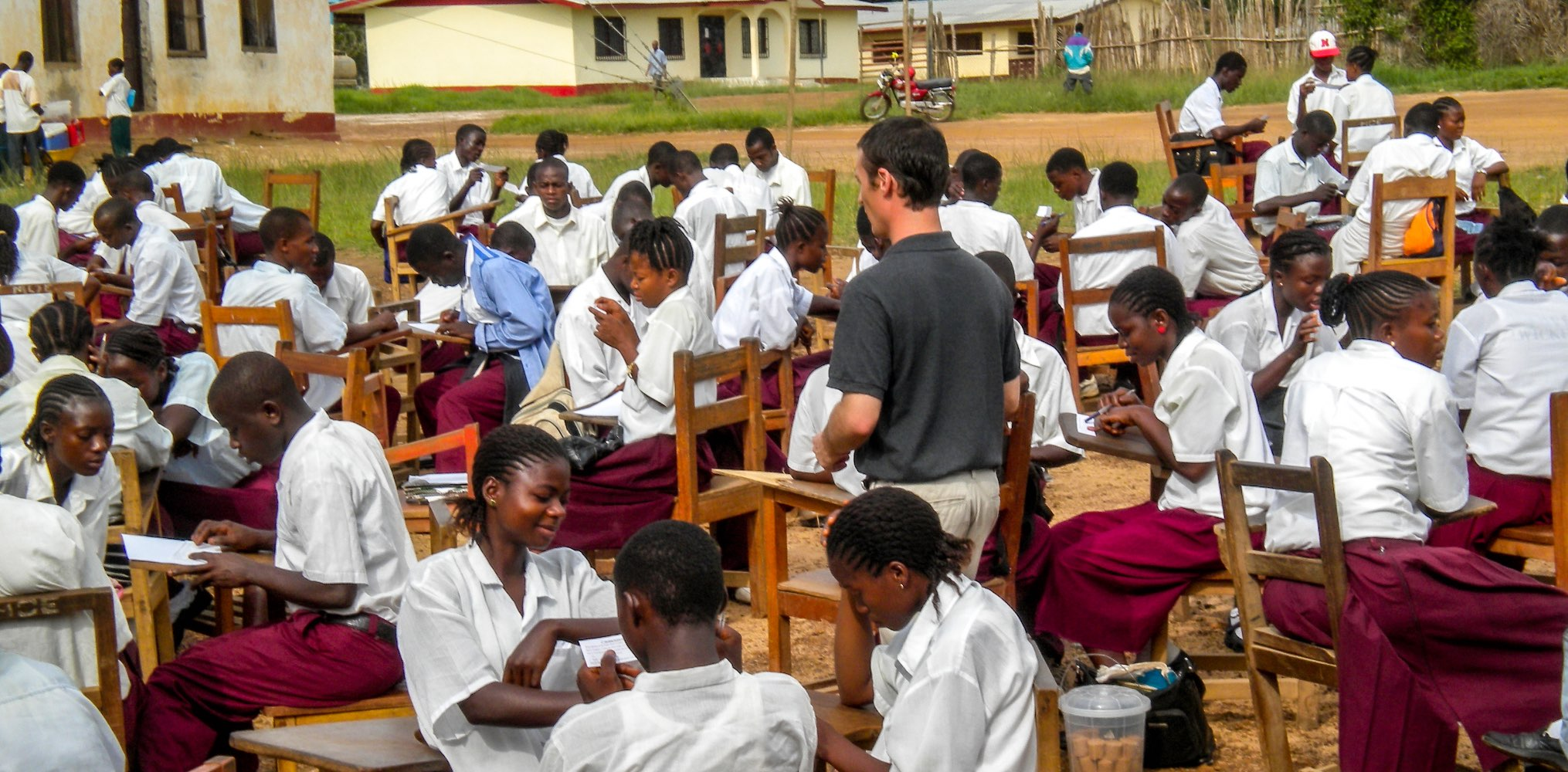 SIT student teaching an outdoor classroom of students in Liberia