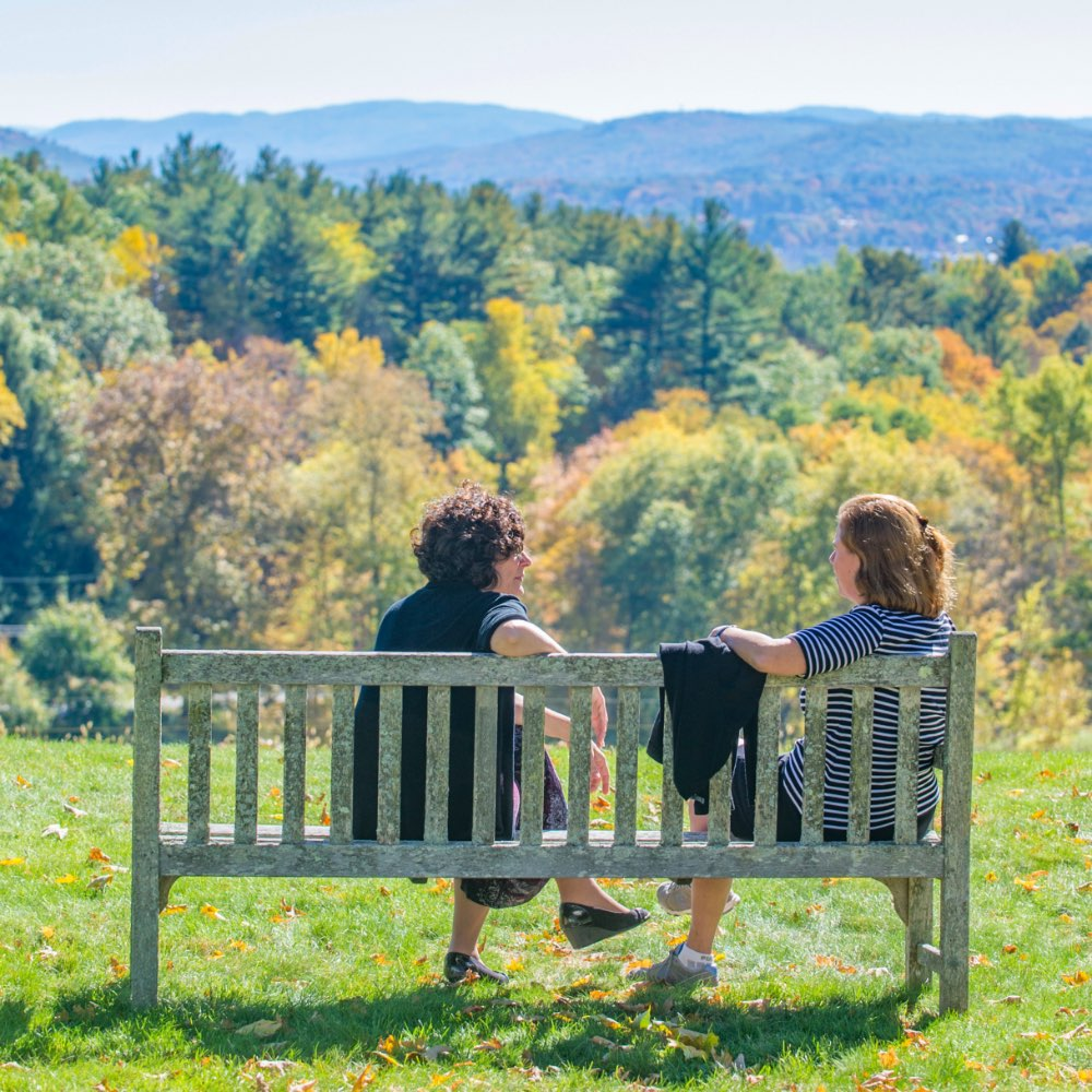 SIT students sitting on a bench on SIT Graduate Institute's Brattleboro, Vermont campus
