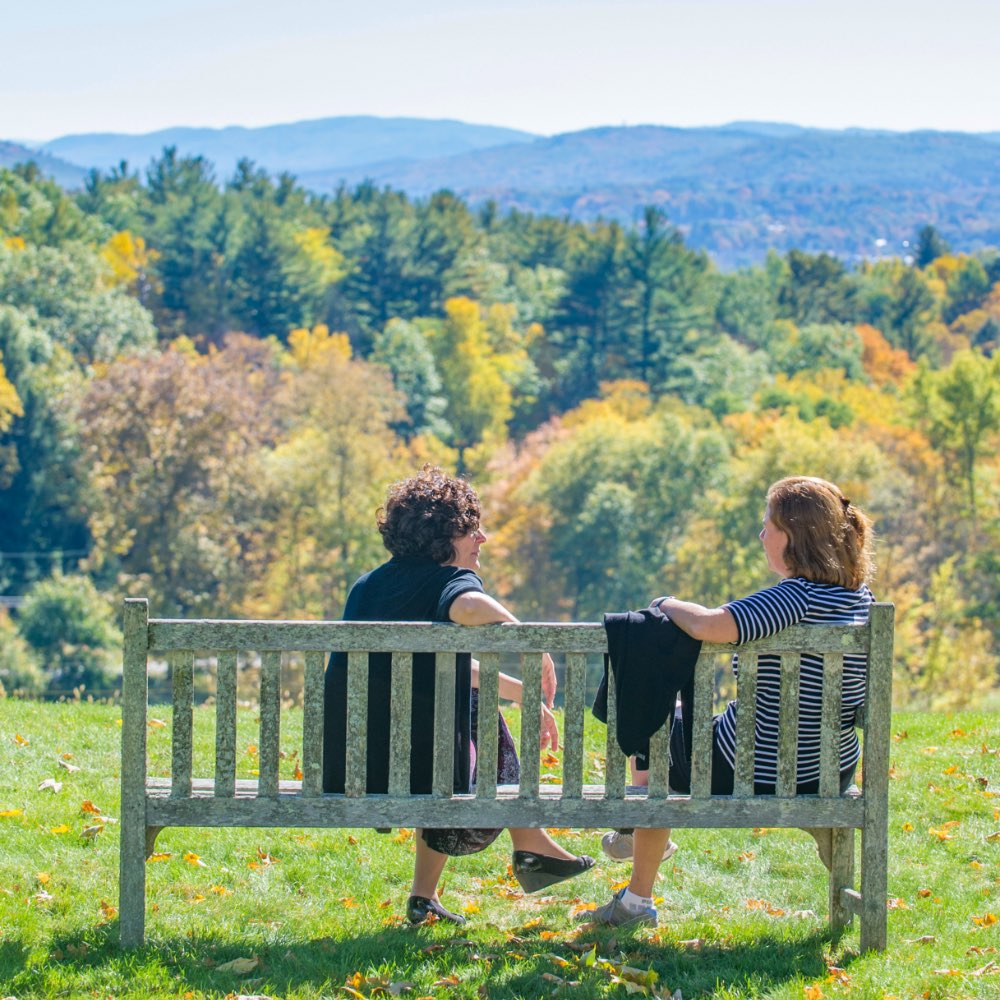 SIT students sitting on a bench on the SIT Graduate Institute campus in Brattleboro, Vermont